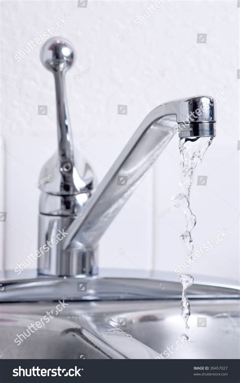 water dribbling from a leaking faucet on the kitchen sink