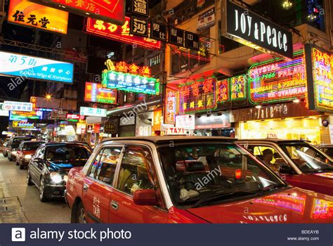Neon Signs And Taxi In Traffic In Tsim Sha Tsui, Kowloon