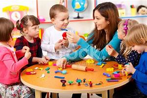 Nursery Teacher Playing With The Kids Stock Photos