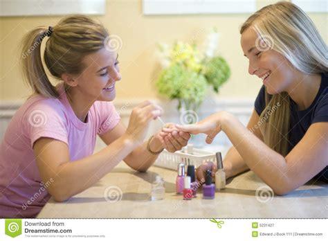 Teenage Girls Putting On Nail Polish Stock Image