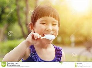 Happy Little Girl Eating Popsicle With Sunset Background