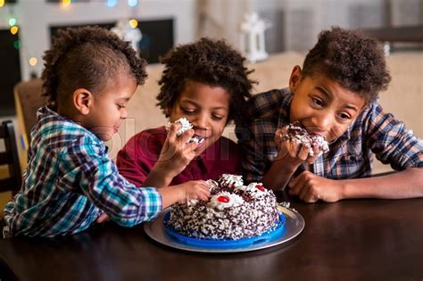 Three afro boys eating cake. Three black kids eat cake