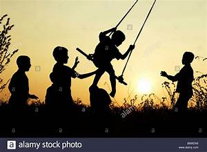 Silhouette of Indian children playing on a home made swing ...