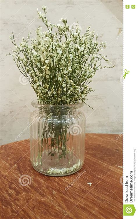 white flower table l small white flowers in clear glass vase on wood table