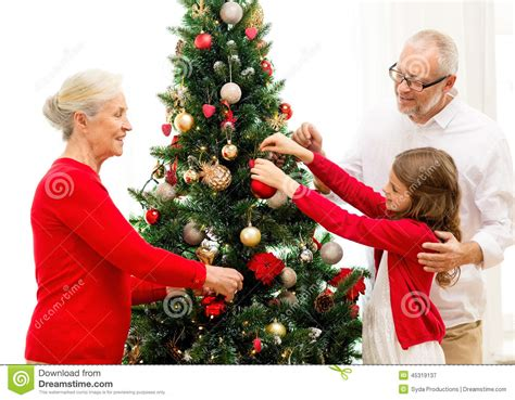 Smiling Family Decorating A Christmas Tree Royalty-free