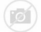 Teresa Celli hugs Gene Kelly in front of officers in a ...