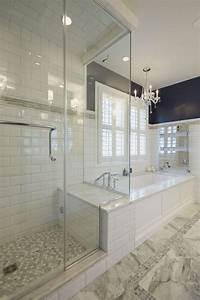 Glass, Enclosed, Shower, With, Bench, Connected, To, The, Platform, Of, A, Soaking, Tub, With, Heated, Towel