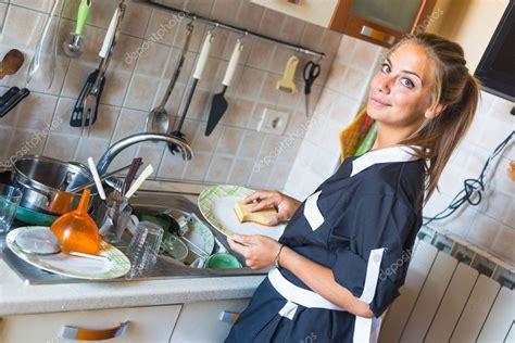 femme dans la cuisine femme de ménage laver la vaisselle dans la cuisine photo