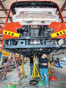 workers install wiring in an electric bus at a byd factory ...
