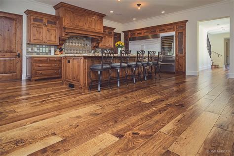 distressed white cabinets rustic wide plank hardwood flooring in kitchen with