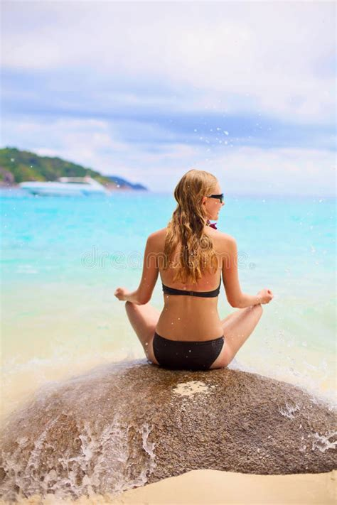 Rock The Boat Video Backwards by Girl Sitting On Stone Backward Near Sea Stock Photo