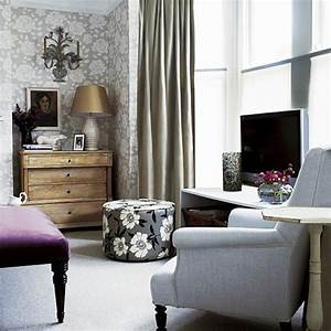 Living room with floral walls, footstool, chair and TV ...