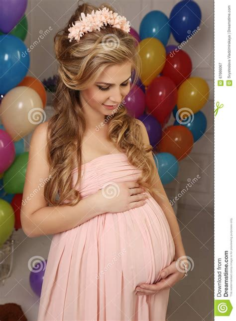Pregnant Woman With Long Blond Hair In Elegant Dress With A Lot Of Colorful Air Balloons Stock