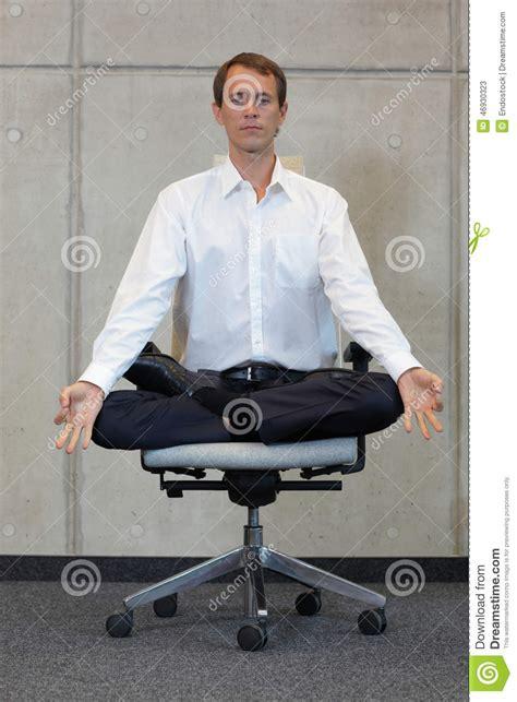 meditating caucasian businessman in lotus pose on office