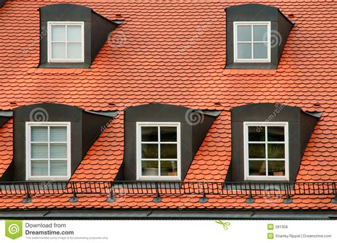 Red Tile Roof And Gabled Dormer Windows On Building In