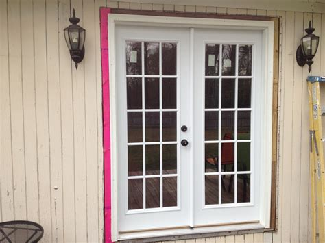 classic white wooden patio glass door with black iron knob