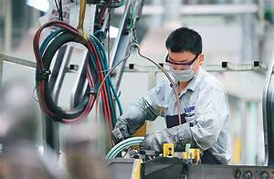 A Worker Performs A Soldering Job At An Auto Manufacturing