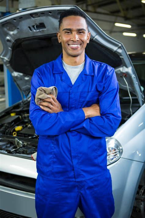 Free Photo | Happy mechanic standing at repair garage