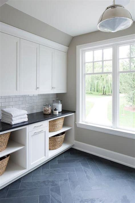 white laundry cabinets  gray slate herringbone floor