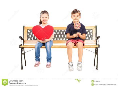 deux enfants assis sur le banc tenant le grand coeur et une lucette photo libre de droits
