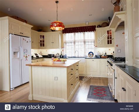 Cream Island Unit And Fitted Cupboards In Country Kitchen