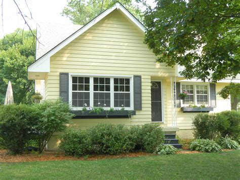 grey shutter pale yellow house landscaping paint