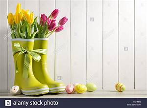 Rain boots, fresh tulips and easter eggs on wood
