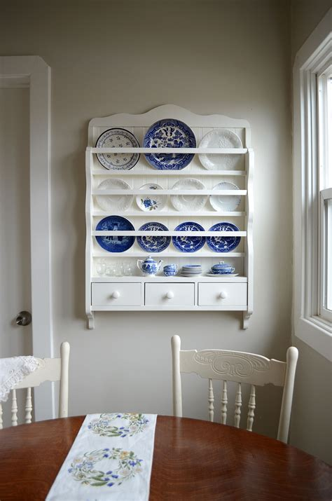 blue  white dishes   white plate rack doesnt    plate rack wall