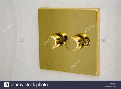 gold metal double electric dimmer light switch on a wall