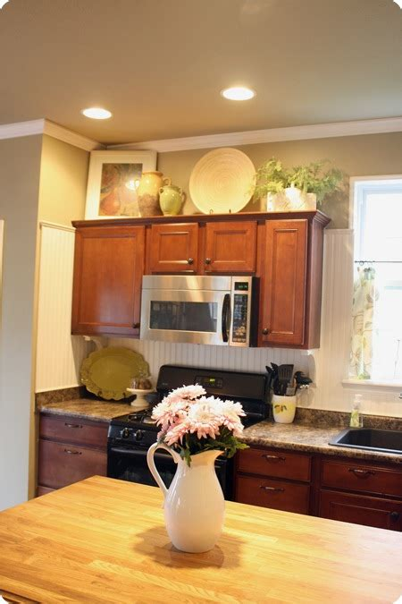 Decorating Ideas For Tops Of Kitchen Cupboards by How To Decorate Above Kitchen Cabinets From Thrifty Decor