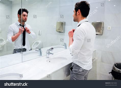 Man Getting Dressed In A Public Restroom With Mirror Stock Photo 94819492