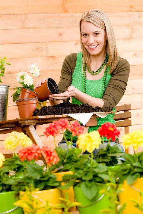 terrazzo in fiore donna di giardinaggio pianta il fiore della sorgente