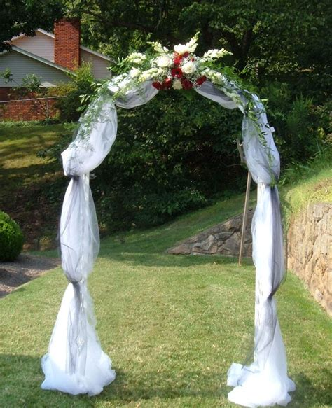Wedding Arch Covered With Tulle And Accented With Flowers