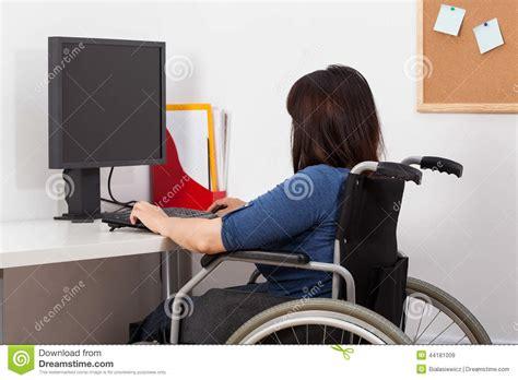 dans le bureau femme sur le fauteuil roulant fonctionnant dans le bureau