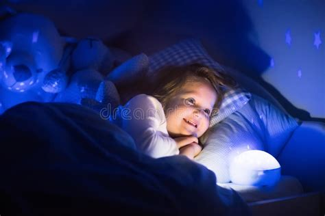 Little Girl Reading A Book In Bed Stock Photo Image