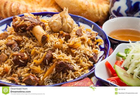 national cuisine of uzbek national food pilaf on traditional fabric adras