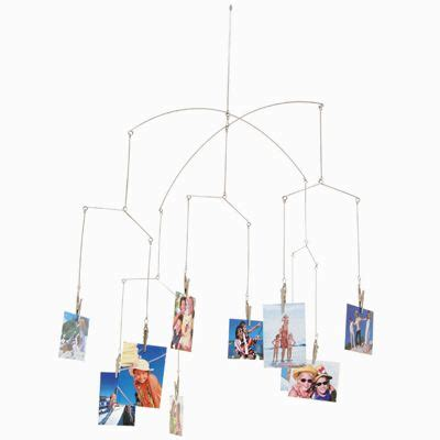 these artie devises hang from above and hold photos via