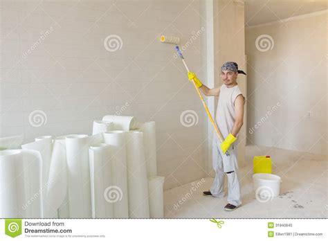 jeune homme avec le papier peint de peinture de rouleau de