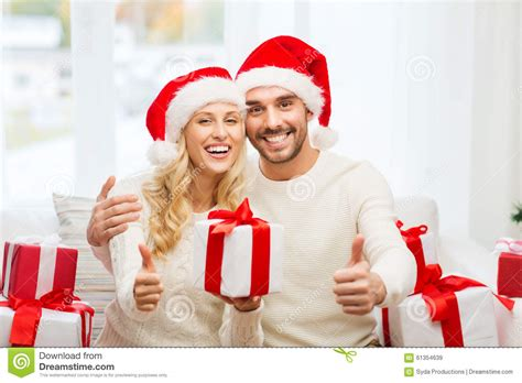 happy couple with christmas gifts and thumbs up stock