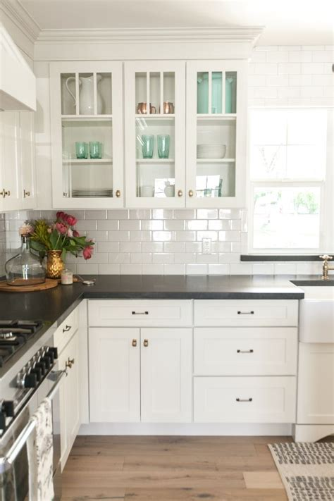 white kitchen with white subway tile white kitchen cabinets black countertops and white subway 2107