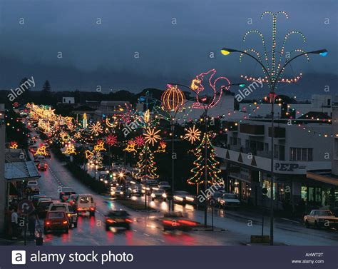 christmas lights and decorations on a wet street busy with