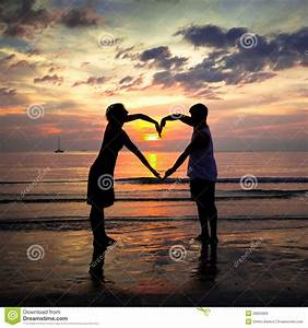 Young Couple Holding Hands Heart-shaped At Sunset Stock ...