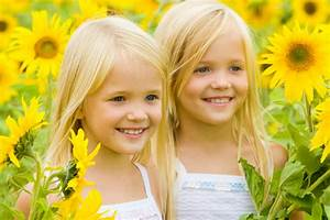 children smiling in a sunflower field - Nature Moms