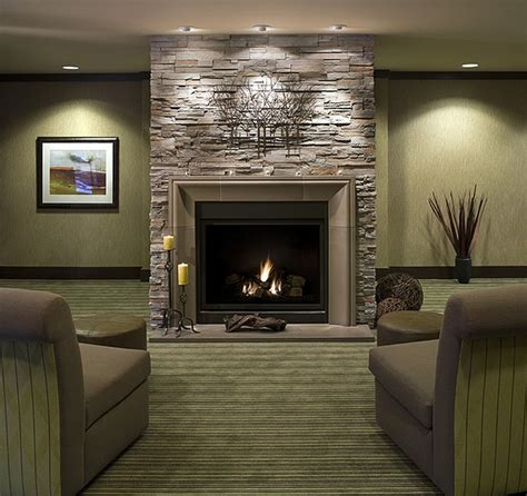 black wood burning fireplace design idea with gray stone wall and yellow candle on black wrought