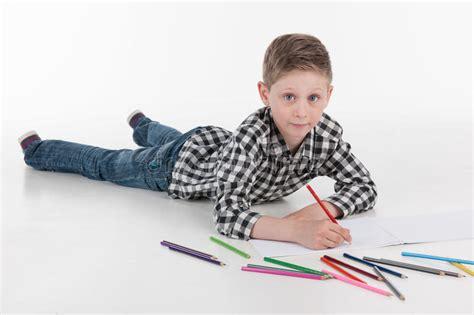 portrait   boy drawing lying   floor stock
