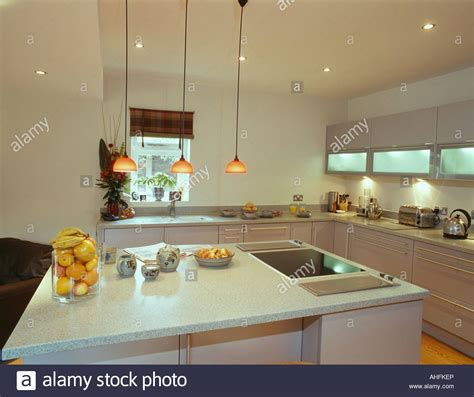 Mobile Kitchen Island Ideas - pendant lights over island unit with halogen hob and oranges in glass stock photo royalty free