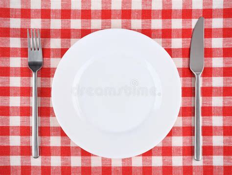 Plate, Fork, Knife On A Red Checkered Tablecloth. Stock