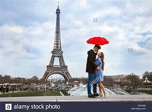 beautiful couple with umbrella near eiffel tower With honeymoon in paris france
