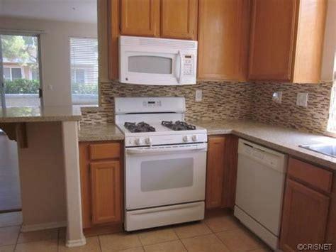 tile backsplash in builder grade kitchen light oak