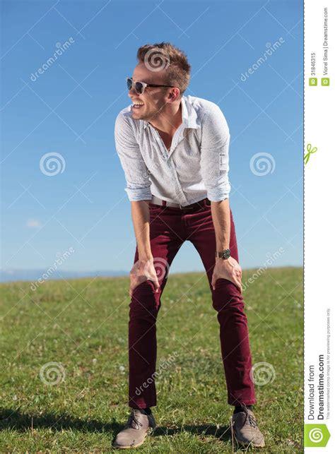 casual man stands outdoor  hands  knees royalty